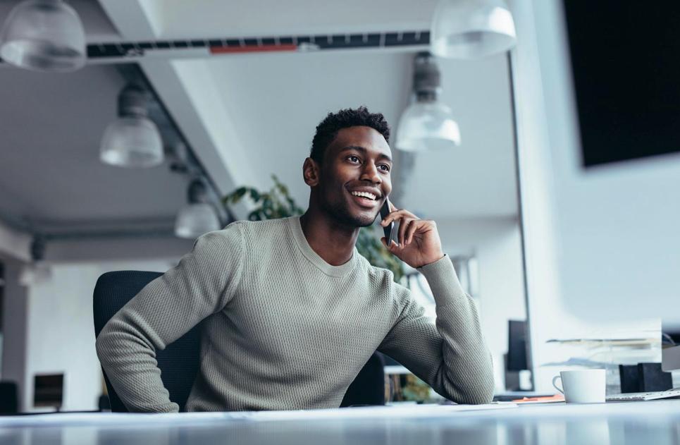 Homme en train de passer un appel à l'aide d'un iPhone pour illustrer la prise de rendez-vous avec une professionnel ALis Business pour la mise en place de votre solution informatique Apple en entreprise