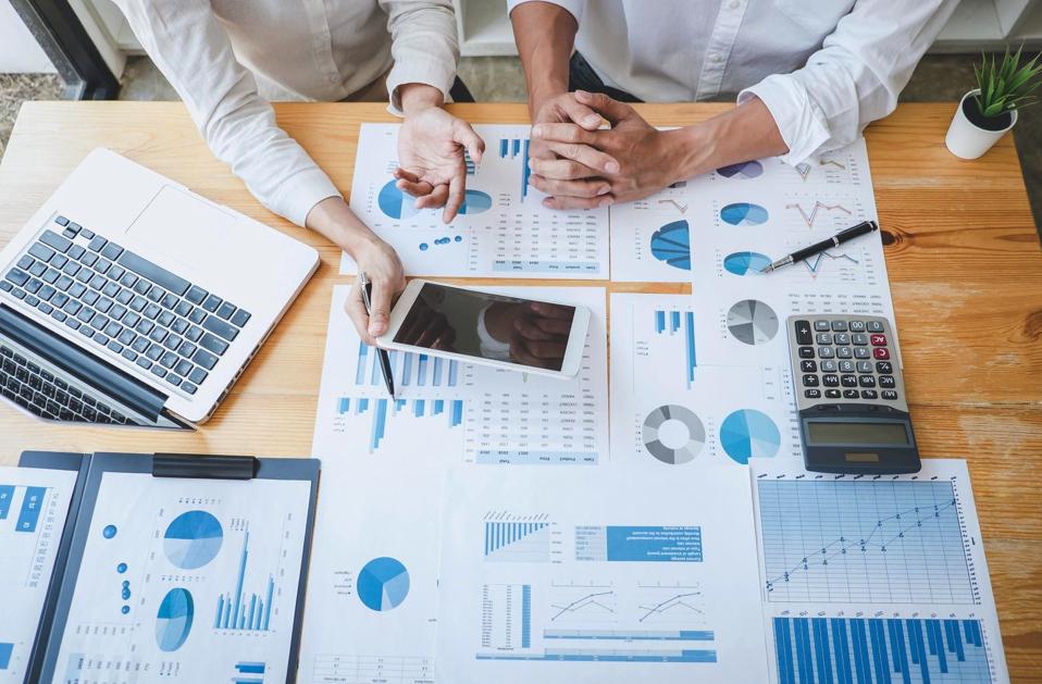 Collègues analysant des graphiques à l'aide d'un MacBook Pro et d'un iPad pour illustrer l'analyse de vos besoins informatiques en entreprise par ALis Business