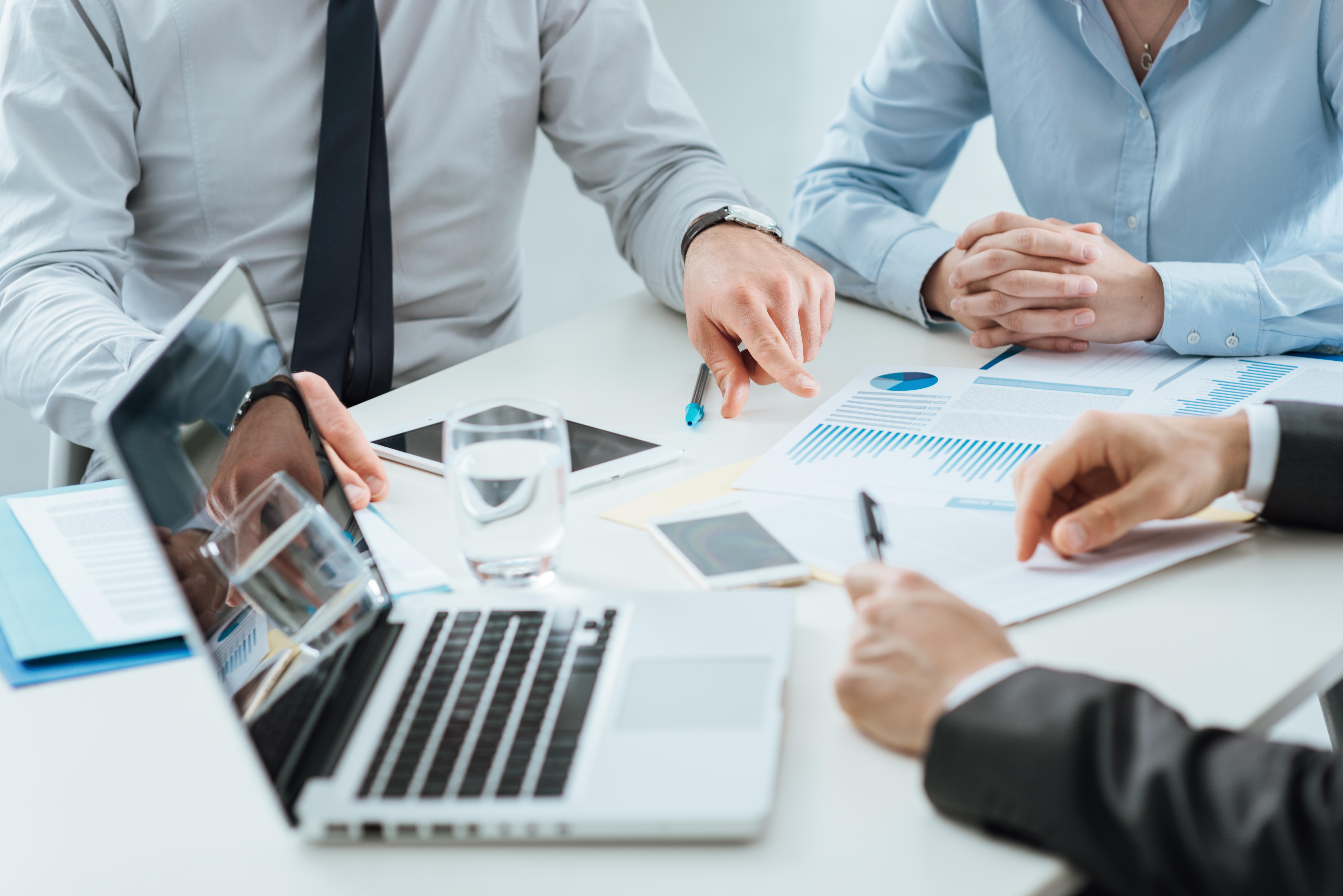 Hommes d'affaires travaillant en groupe avec un MacBook, un iPad et un iPhone pour illustrer la facilité d'utilisation des produits Apple en entreprise selon ALis Business