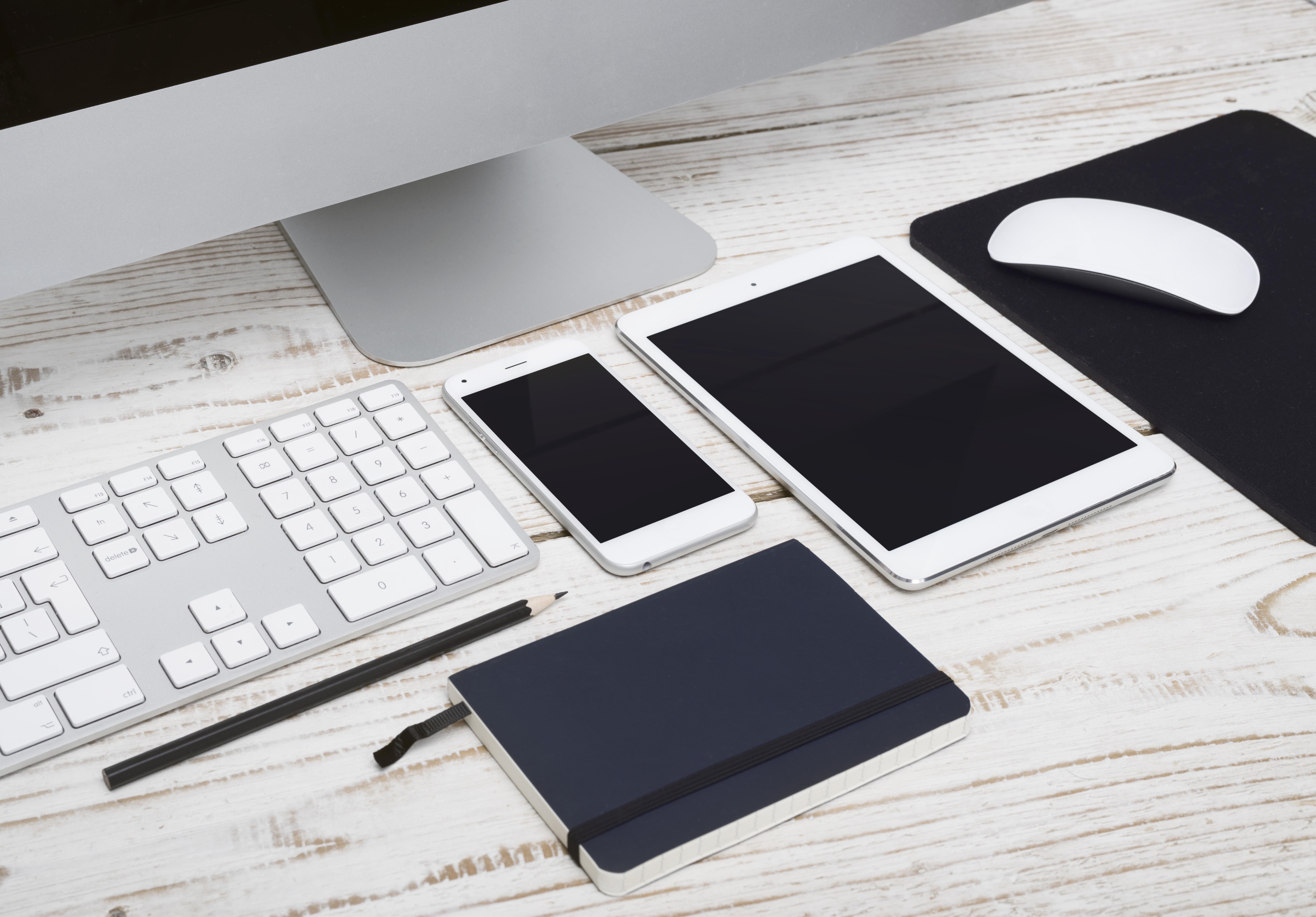 Ordinateur Mac, iPhone et iPad sur un bureau pour illustrer l'interconnectivité des produits Apple en entreprise selon ALis Business