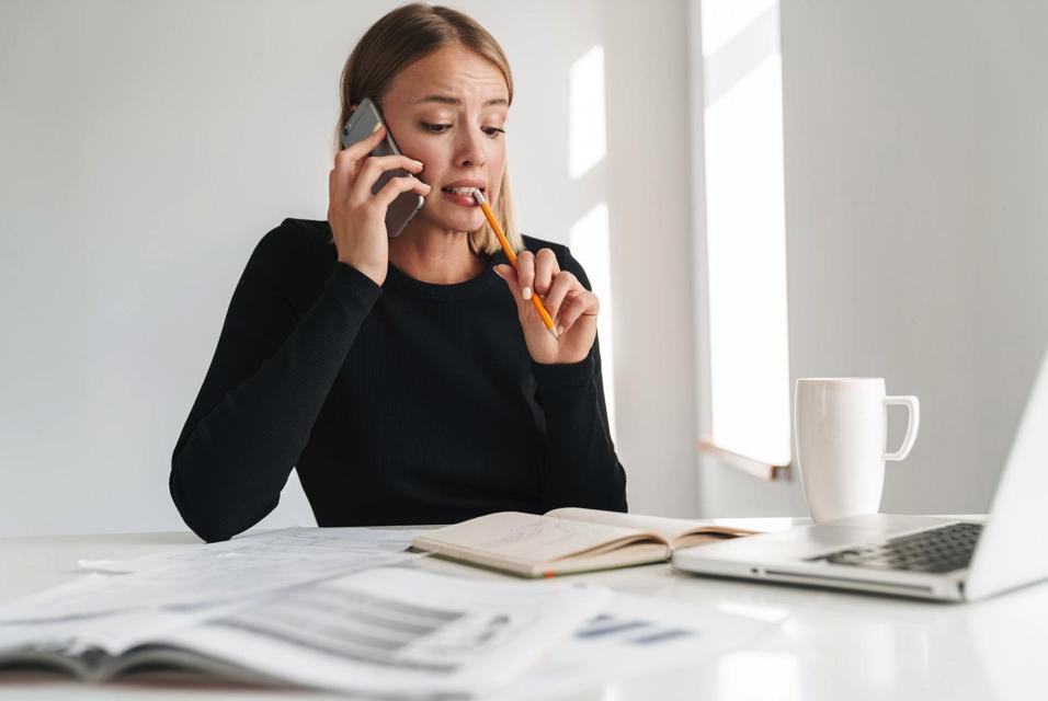 Femme peu sûre d'elle en train de téléphoner avec un iPhone devant son MacBook Pro pour illustrer le choix difficile de la solution informatique en entreprise avec ALis Business