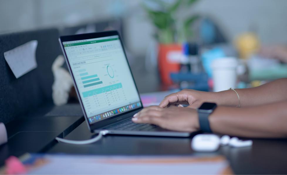Personne utilisant un MacBook avec un fichier Excel ouvert pour illustrer la compatibilité des produits Apple avec les logiciels informatiques usuels selon ALis Business