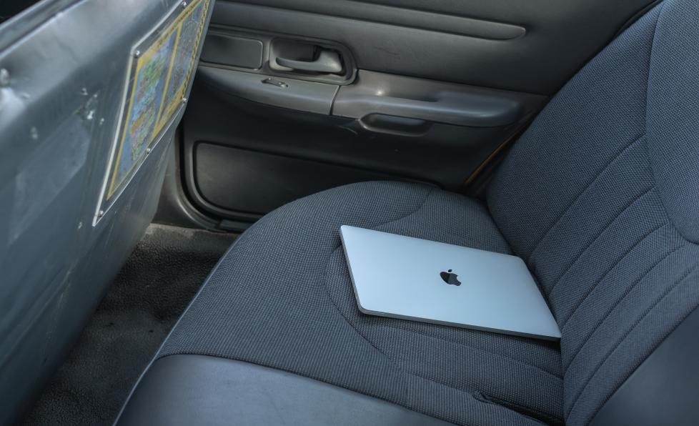 Ordinateur portable sur le siège d'une voiture pour illustrer la garantie de sécurité des données des appareils Apple par ALis Business