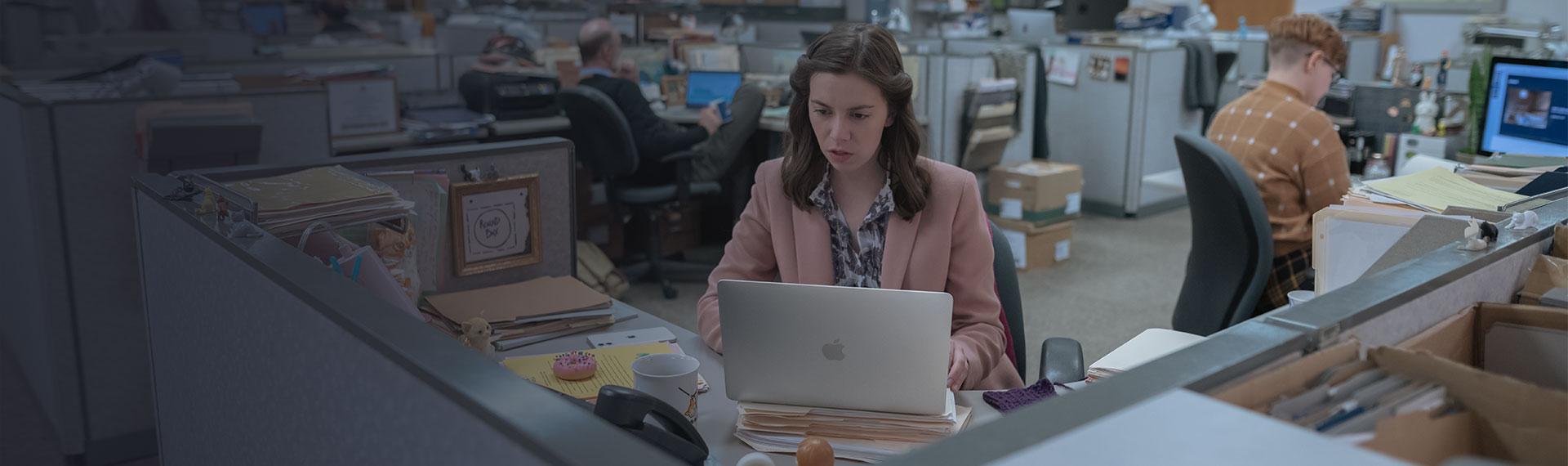 Femme qui travaille sur un MacBook dans un openspace pour illustrer les solutions informatiques Apple en entreprise selon ALis Business